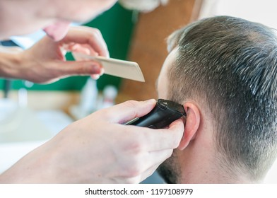 young man in barbershop. Closeup portrait of man getting haircut from hairdresser.