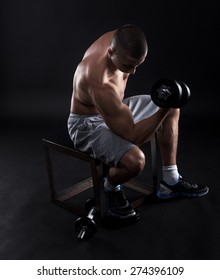 Young man with bare chest lifting dumbbells on black background.