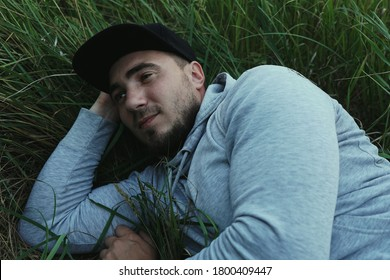 A young man in a baseball cap lies in the green grass. The unity of man with nature.