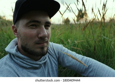 Young man in a baseball cap on a background of grass with a cane in his mouth. The unity of man with nature.