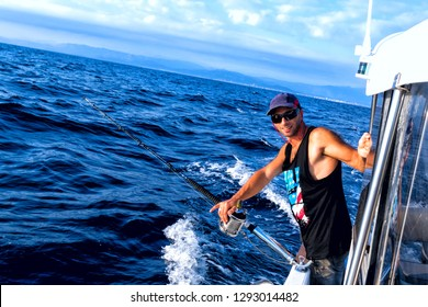 The young man in a baseball cap onboard the vessel in the course of fishing against the background of the blue sea.