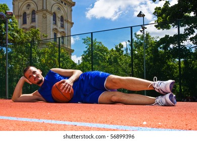 Young man with basketball ball relaxes