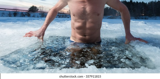 Young man bathing in the ice hole. Focus on the ice in a water only