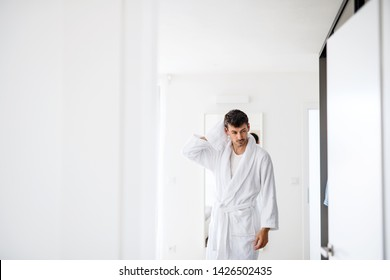 Young man with bathrobe in the bedroom, a morning routine.