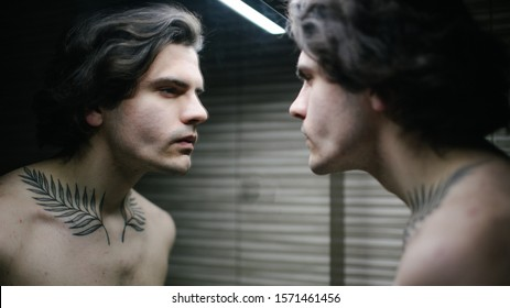 Young man in bathroom looking into a mirror at himself. He has a tattoo over his neck