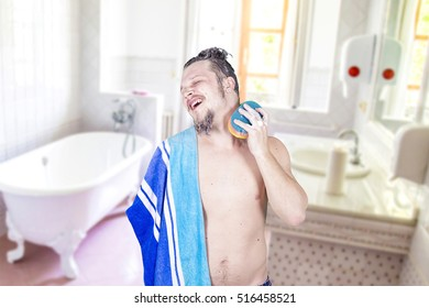 Young man in the bathroom with a towel