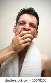 young man in bathroom with white towel around his neck yawning