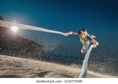 Young Man with battle ropes exercise on the beach. Cross Fitness on the sand in night.