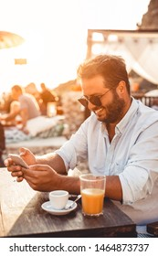 Young man at beach cafe drinking coffee and using mobile phone