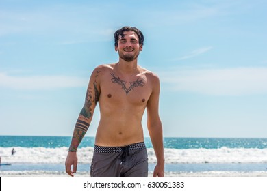 Young man at the beach coming out of the ocean