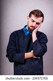 young man with beard in blue sweater dozing
