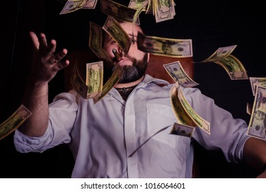 Young man with a beard and a cigar smoking. Flying dollars with a man on a black background.