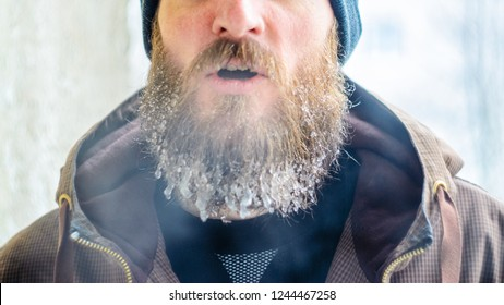 Young man with a beard covered with icicles and frozen droplets on the street after exercise. Evaporation from the mouth in winter