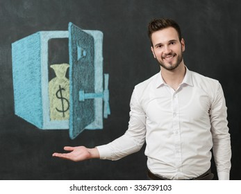 young man with beard in front of safe smiling and showing money