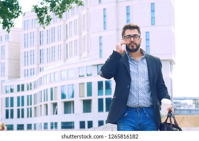 Young man with beard in glasses holding coffee cup and talking on mobile phone while walking outdoors.