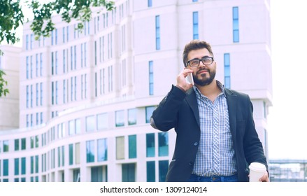 Young man with beard in glasses holding coffee cup and talking on mobile phone while walking outdoors. Always in touch.