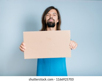 A young man with a beard is holding a cardboard for inscriptions, an isolated studio photo on the background
