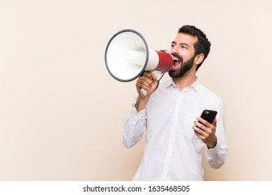 Young man with beard holding a mobile shouting through a megaphone