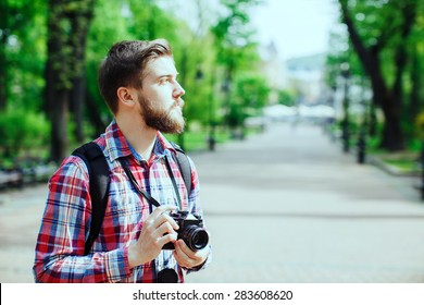 Young man with a beard holding old film camera and looking to the side, outdoors in the alley, in the park, profile