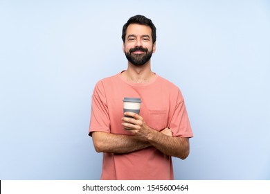 Young man with beard holding a take away coffee over isolated blue background keeping the arms crossed in frontal position