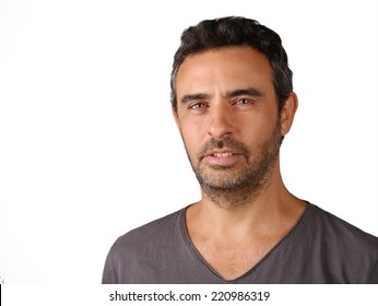 Young man with beard looking at the camera against white background