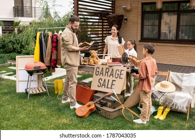 Young man with beard looking through book while choosing it at yard sale, woman and her kids waiting for customers answer