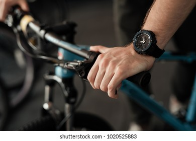 A young man with a beard looks at the details of the bicycle in the bicycle store. He carefully examines every detail.
