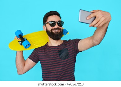 young man with beard making a selfie over blue background while holding a skateboard. Colorful concept
