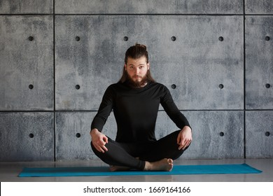 A young man with a beard practices yoga in the gym.