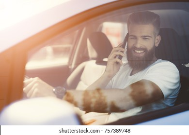 A young man with a beard sits at the wheel of an electric vehicle. He is focused on the road. He feels confident in the cabin of this car.