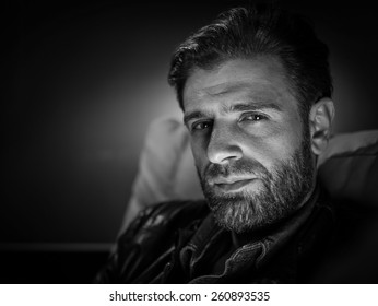 Young man with beard sitting on sofa at home