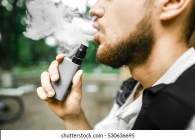 A young man with a beard smoking electronic cigarette