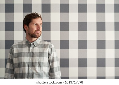 Young man with a beard standing in front of checkered wallpaper and wearing a matching shirt