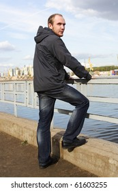 young man with beard standing on river embankment and looking back