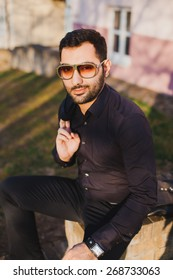 young man with beard and sunglasses posing on the street with a jacket in his hands