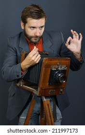 the young man with a beard taking photos with vintage camera