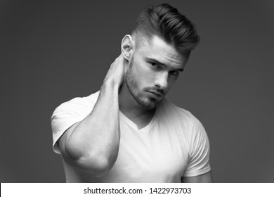 young man with a beard. A man in a t-shirt. Male portrait on a gray background. Stylish man. black and white photo. Sports man. male fitness model. studio portrait