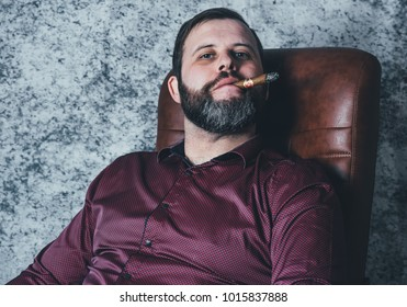 Young man with a beard and a watch smoking cigar on a grey background