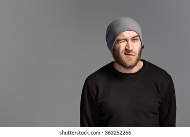 a young man with a beard wearing a hat on a gray background with the emotion on his face