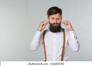 A young man with a beard in a white shirt and yellow suspenders and pants touches his beard and mustache on a gray background