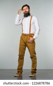 A young man with a beard in a white shirt and yellow suspenders and pants on a gray background