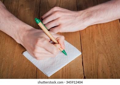 Young man with beard writing on napkin