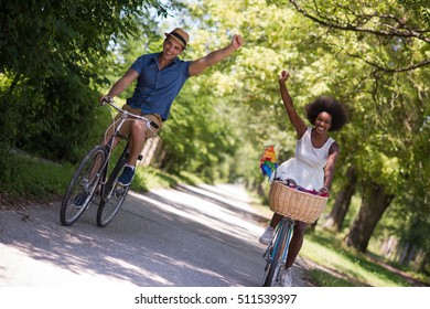 a young man and a beautiful black girl enjoying a bike ride in nature on a sunny summer day