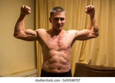 A young man with a beautiful muscular body does morning exercise in his apartment and poses for the photographer