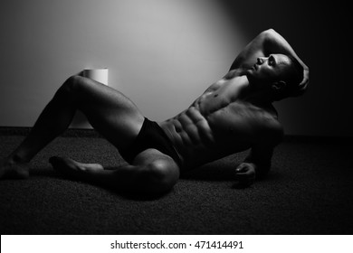 Young man with beautiful muscular torso in underwear lying on floor, black and white