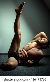 Young man with beautiful sexy muscular torso in underwear lying on floor with raised leg
