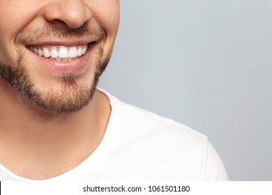Photo of Young man with beautiful smile on grey background. Teeth whitening