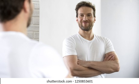 Young man with beautiful sports figure examining his reflection in mirror