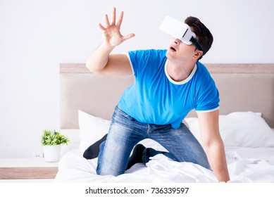 Young man in bed wearing a vr virtual reality head set