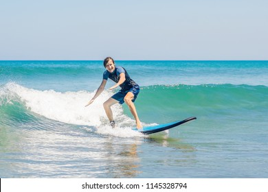 Young man, beginner Surfer learns to surf on a sea foam on the Bali island.